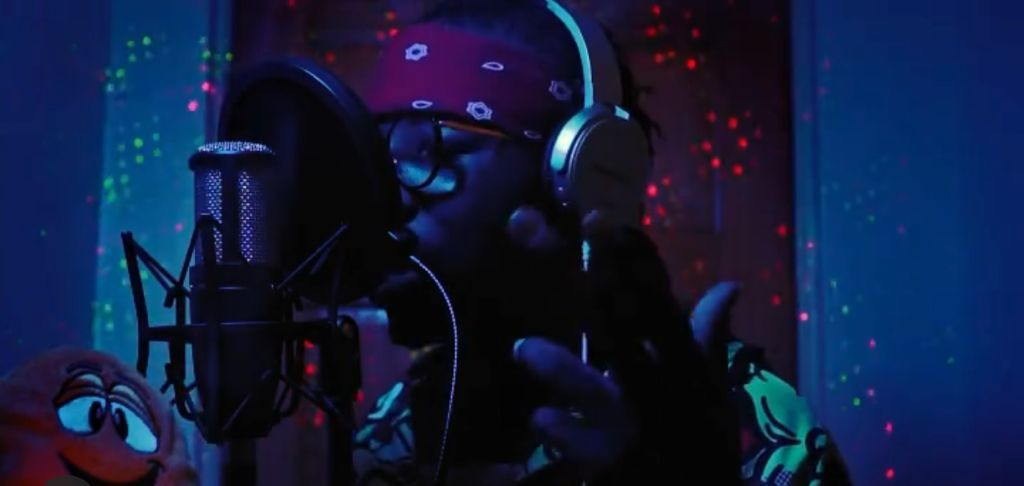 A Screen capture of Bermuda artist Clazzic rapping in latest video